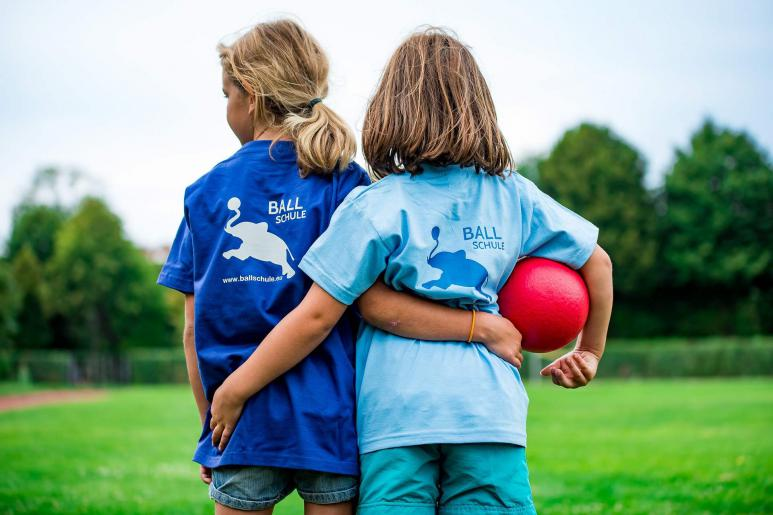 Zwei Mädchen von hinten, die sich von hinten umarmen und einen Ball in der Hand halten